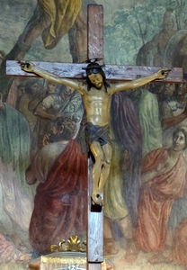 Crucifix sixteenth century against the background of the frescoes by Luigi Ademollo